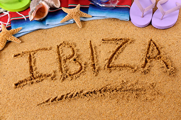 The word Ibiza written on a sandy beach, with scuba mask, starfish and flip flops (studio shot - warm color and directional light are intentional).